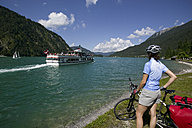 Austria, Tyrol, Achensee, Woman with mountainbike watching out on lakeshore - DSF00134
