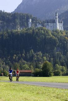 Germany, Bavaria, Neuschwanstein Castle, Couple mountain biking - DSF00116