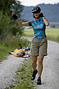 Germany, Bavaria, Oberland, Woman gesturing, fallen biker in background - DSF00110