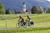 Germany, Bavaria, Couple mountain biking across highway - DSF00107