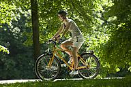 Germany, Bavaria, Munich, Woman mountain biking across park - DSF00098