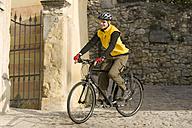 Italy, Trento, Torbole, Mountaibiker riding across lane - DSF00086