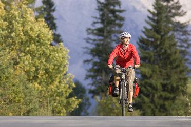 Austria, Tyrol, Ahornboden, Mountainbiker riding across highway - DSF00068
