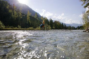Austria, Tyrol, Ahornboden, Mountainbiker standing on the waterfront - DSF00065