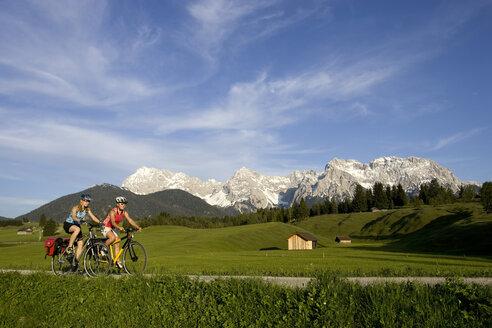 Germany, Bavaria, Mittenwald, Two women mountain biking across highway - DSF00047