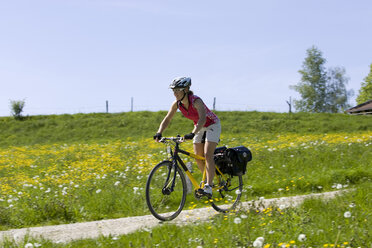 Germany, Bavaria, Oberland, Woman mountain biking across farm track - DSF00041