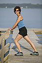 Germany Bavaria, Tutzung, Woman on landing stage stretching leg - DSF00032