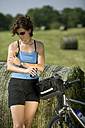 Germany, Bavaria, Seeshaupt, Woman with mountain bike applying sun cream - DSF00029