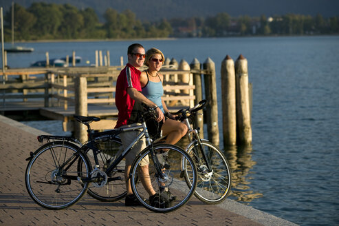 Germany, Bavaria, Tegernsee, Couple with mountain bikes on the lakefront - DSF00020