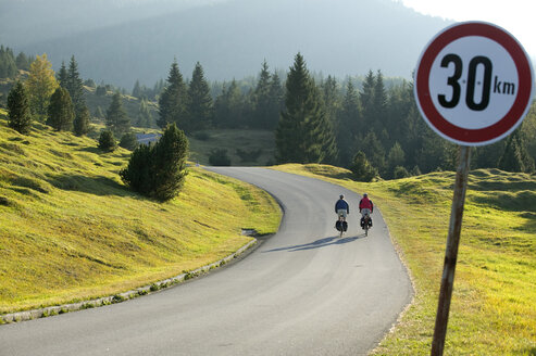 Germany, Bavaria, Mittenwald, Couple mountain biking, traffic sign in foreground - DSF00011