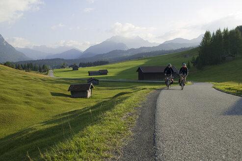 Germany, Bavaria, Mittenwald, Couple mountain biking across highway - DSF00008