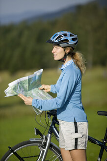 Germany, Bavaria, Mittenwald, Woman with mountain bike holding map - DSF00005