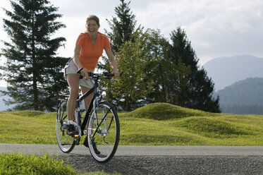 Germany, Bavaria, Mittenwald, Woman with mountainbike, smiling - DSF00002