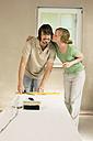 Young couple renovating, Woman kissing man - WESTF09174