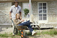 Young couple at construction site, man pushing woman in wheelbarrow - WESTF09159