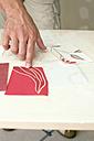 Hand pointing at wallpaper samples - WESTF09110