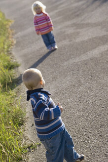Little girl (2-3) and boy (1-2) playing on path, rear view - SMOF00150