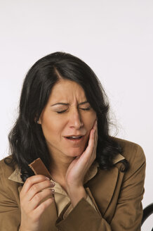 Young woman holding chocolate bar, having toothache, portrait - NHF00937