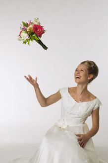 Young bride tossing bridal bouquet, laughing - NHF00918