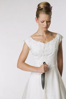 Young bride holding knife, portrait - NHF00907