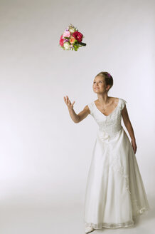 Young bride tossing bridal bouquet - NHF00895