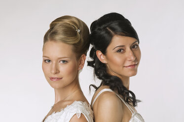 Young brides standing back to back, portrait - NHF00883