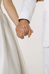 Bride and groom holding hands, mid section, close-up - NHF00869