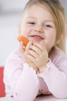 Little girl (3-4) holding a carrot, portrait, close-up - SMO00238