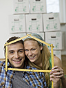 Young couple making house shape with rulers, portrait - WESTF09797