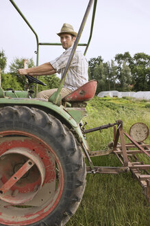 Farmer on tractor ploughing field - BMF00499