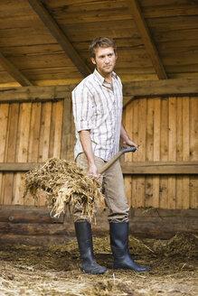 Farmer shovelling hay in barn - BMF00445