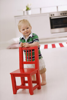 Baby boy (1-2) standing behind red chair - SMO00370