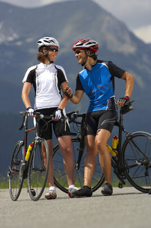 Germany, Bavaria, Mittenwald, Couple with mountain bikes, talking - MRF01113