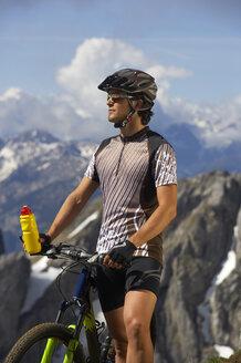 Germany, Bavaria, Karwendel, Man with mountain bike and water bottle - MRF01095