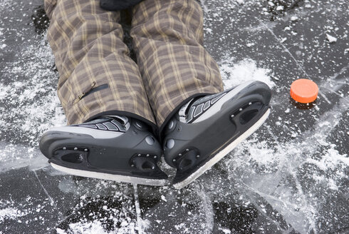 Person with skates lying on frozen lake alongside ice hockey puck, elevated view - AWDF00294