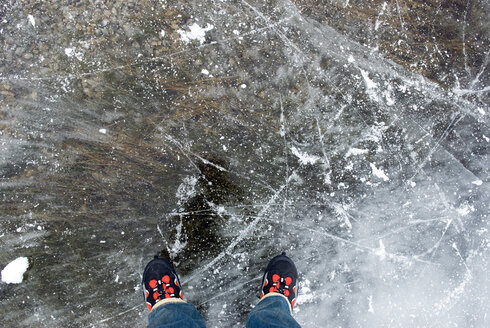 Person with skates standing on frozen lake, elevated view - AWDF00288