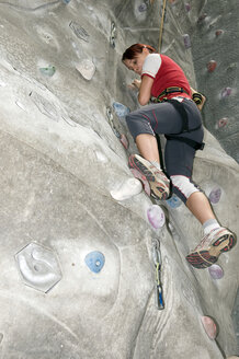 Young woman on indoor climbing wall, low angle view - AWDF00164
