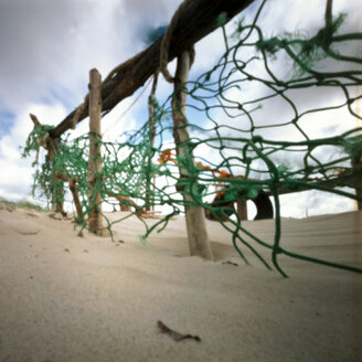 Germany, North Sea, Amrum, Tattered fishing net on the beach - AWD00305