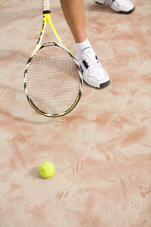 Man holding tennis racket, ball on ground - UKF00164