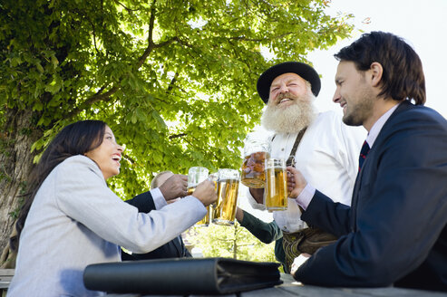 Germany, Bavaria, Upper Bavaria, People in beer garden, clinking glasses - WESTF09724