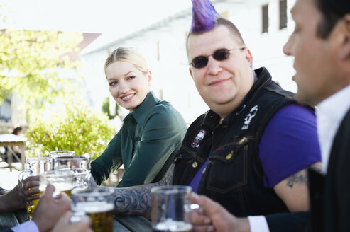 Germany, Bavaria, Upper Bavaria, Business people and punk in beer garden, smiling - WESTF09718