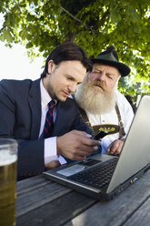 Germany, Bavaria, Upper Bavaria, Senior Bavarian man and young businessman with laptop in beer garden - WESTF09703