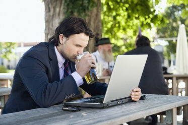 Germany, Bavaria, Upper Bavaria, Young business man in beer garden drinking beer - WESTF09694