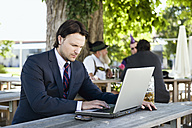 Germany, Bavaria, Upper Bavaria, Young business man in beer garden using laptop - WESTF09691