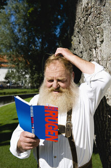 Germany, Bavaria, Upper Bavaria, Bavarian man reading travel book, close-up - WESTF09688