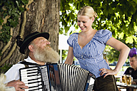 Germany, Bavaria, Upper Bavaria, Senior man in traditional costume playing accordion in beer garden - WESTF09661