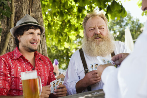 Germany, Bavaria, Upper Bavaria, Men playing cards in beer garden - WESTF09643