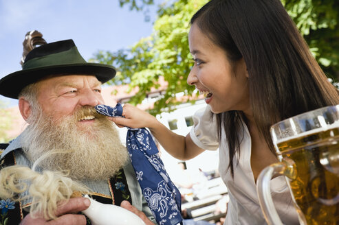 Germany, Bavaria, Upper Bavaria, Bavarian man and Asian woman in beergarden, Asian woman wiping man's beard - WESTF09634