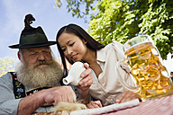 Germany, Bavaria, Upper Bavaria, Bavarian man and Asian woman in beer garden, Bavarian man sniffing snuff - WESTF09631