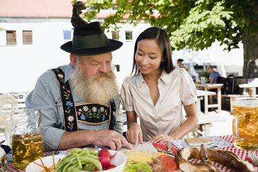 Germany, Bavaria, Upper Bavaria, Asian woman and bavarian man in beer garden - WESTF09624